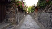 quioto : lady walking fast in Japanese alley with stone road and rock walls around Vídeos