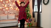 cloche : cute christmas girl in red dress cheerful jumping with her new gift. dancing in the cozy living room with a decorated christmas tree in the background. xmas celebration concept.