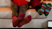 girl left : Young mom and child in matching christmas socks on couch indoors. closeup of two feet with colorful socks moving left and right. family celebrates xmas at home reading storybook.
