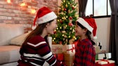 happy new year : mom and cute daughter celebrate christmas eve in cozy living room. young mother and little girl holding hands and shaking hands happily. celebrate christmas at home concept.