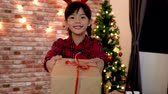 girl left : lovely kid with deer on head joyfully sending present. cute girl dancing holding gift box moving left and right. child having fun in the living room on christmas eve. Stock Footage