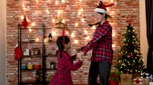 satisfeito : young mom and daughter with christmas dressed joyfully having fun in the living room. family holding hands and dancing in circle at home. family celebrate xmas eve lifestyle.