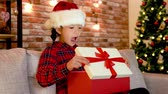 parede de tijolos : christmas tree beside and lights on the red brick wall in the background. cute kid sitting on the couch and opening her xmas gift box. shining gift in the present box little girl with surprised face.