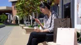 alto : asian lady sitting outdoor laughing having fun in holidays. joyful young girl using cellphone app chatting with friends. lifestyle woman relaxing enjoying sunny day with shopping bags beside.