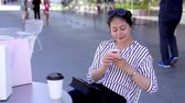 alto : asian young business woman relaxing outdoor using smartphone app texting sms message. elegant office lady with sunglasses sitting in sunny day online clothes shopping. coffee and bags on the table. Stock Footage
