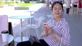 alto : young lady relaxing sitting chair outdoor and looking around. asian girl using cellphone app shopping online while is summer sale. nice weather with winds blowing. Stock Footage