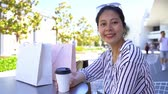 alto : young Asian woman resting drinking coffee and attractive smiling to camera. elegant office lady in holdiday shopping in christmas sale alone. happy girl sitting outdoor with many bags beside.