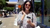 alto : young happy lady smiling at the camera after  shopping in summer sale and buying lots of bargain purchase in clothes shops. girl holding cup of coffee on sunny day. special price in the mall concept. Stock Footage