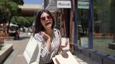alto : young girl happy holding shopping bags walking stanford shopping center. asian lady excited with the christmas sale. elegant woman outdoor in sunny day.
