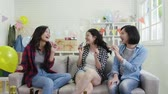 assobio : group of cheerfully young girls with blowers having fun at house party in bright decorated living room. best sister playing with toys and balloons relaxing on couch presents gifts boxes beside.