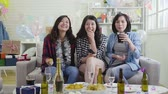 pískat : group of young female friends drinking beer eating chips and watching tv at home party. happy girls relaxing laughing in living room with birthday gifts beside. alcohol beer wine champagne on table.