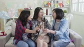 eğlenmek : slow action friends toasting alcohols champagne beer room full of colorful confetti. group of happy girls cheers celebrating birthday in house party. decorated living room with balloons and presents. Stok Video