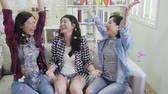 assobio : slow motion of carefree girls raising up hands playing with colorful confetti in decorated house with balloons. young friends celebrating new year at home. young people chilling on couch living room