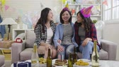 engarrafado : happy party young girls hugging together at house birthday party laughing chatting in decorated living room at home. beautiful asian women friendship celebrate with gifts and alcohol during holiday
