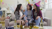 szampan : slow motion of young asian girlfriends sitting on couch cheerfully talking and hugging with love. group of best friends at house party celebrating birthday in the day. happy ladies enjoy gathering.