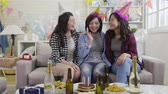 engarrafado : slow motion of young asian girlfriends having fun in home living room. happy ladies with funny hats enjoying time together chatting celebrating birthday party in decorated house full of balloons.