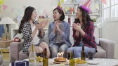 engarrafado : young ladies happily singing songs celebrating birthday at home. house party with burning candles on cake surrounding champagne. joyful attractive asian women clapping hands on sofa indoor.