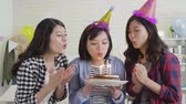 lánytestvér : young female asian with colorful hats celebrating birthday party at house indoor. beautiful girls clapping hands holding cake and blowing candles together. cheerful ladies laughing during home life. Stock mozgókép