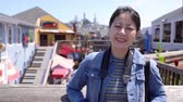 caído : Cheerful woman traveler face to camera smiling lovely. young girl toursit standing outdoor relaxing on sunny day enjoying sunshine. beautiful asian student travel in san francisco on summer vacation. Stock Footage