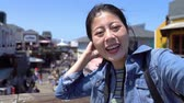 caído : asian girl chatting on video phone app outdoor waving hands saying goodbye. young lady tourist self guided trip in san francisco and shopping on summer sale in pier 39 mall on sunny day blue sky. Stock Footage