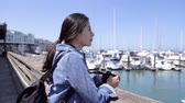 caído : young lady lens man holding camera enjoying the beauty of the ocean nature view on pier 39. girl photographer visit famous destination fisherman wharf in san francisco and relaxing sightseeing sunny.