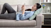 tragédia : young office lady tired relaxing lying on sofa after work. happy businesswoman back to home resting using smartphone texting message cheerfully. lazy pretty girl on weekend lifestyle concept. Stock Footage
