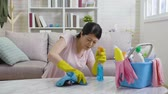 paçavra : slow motion of young housewife trying hard to remove the dust on marble table in living room. housekeeper wearing yellow protective gloves using rag wiping cleaning sitting on floor concept.