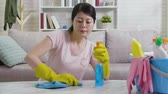 postřikovačů : Young housewife in gloves is cleaning table with detergent. asian mom frowning spraying cleaner wiping the table by blue rag in living room. wife sitting on floor with bucket full cleaning supplies.