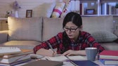 napló : slow motion of girl student writing memo note on book. young asian woman in glasses studying late at night in living room sitting on floor home. text books and calculator on table prepared for exam