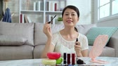 introduce : Young beauty blogger recording video indoors teaching makeup tutorial online streaming. asian woman vlogger showing mascara in live at home. beautiful female chinese talking to camera introducing.
