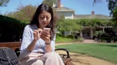 rychlý : fast action elegant asian woman smiling using cellphone relaxing outdoors. young female using mobile phone texting sms message sitting on bench chair in garden in house on sunny day enjoy sunlight Dostupné videozáznamy