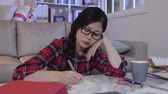 stay : Thoughtful asian young woman studying reading in dark living room. tired girl college student thinking about new idea writing down on notebook. bored teenager say up late in midnight hard working. Stock Footage