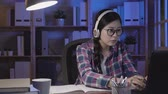 репетитор : slow motion asian student girl using online education service at home at late night. Young woman looking in laptop display typing keyboard watching training course and listening it with headphones.