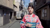 gueixa : young local japanese lady elegant confident in kimono dress walking on urban city street on sunny day. beautiful woman wearing traditional costume going to visit family new year celebration festival