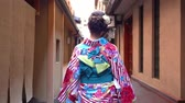gueixa : fast forward of young japanese girl in kimono dressing walking in the path to festival. back view lady in colorful beautiful traditional costume going pass by the house wooden door in hanamikoji dori Vídeos