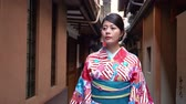 geisha : elegant beautiful kimono dressing traveler girl walking along in little path in japan. young japanese lady wearing traditional costume seeing around in hanamikoji dori in kyoto japan. Stock Footage