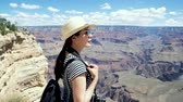 day : young girl backpacker in sunglasses sightseeing beautiful desert view from top of the mountain. lady toursit hiker carrying bag turning around overlooking visiting Grand Canyon National Park.