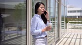varanda : Young asian woman worker with coffee cup talking on mobile phone outdoor white building office terrace. elegant lady employee having break time in the city urban lifestyle in usa with blue sky.