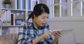 phone bad : young girl relax watching series online in sofa at home shocked surprised by error of cellphone. asian lady unsatisfied with bad internet connection wifi in house. film stopped on smart phone.