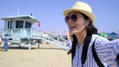 salvaguardar : fast motion chinese girl recording travel video by  showing safeguard stand on beach bay Santa Monica Pier.