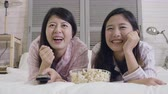 pipoca : slow motion two asian female friends laughing lying on bed in cozy bedroom holding tv control remote watching humor talk show. happy young girls eating popcorn junk food relaxing in apartment. Stock Footage
