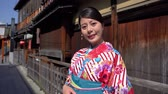 gueixa : attractive asian woman wearing kimono walking on old street in ishibe alley in kyoto. young japanese girl in traditional dress face camera smiling lovely standing next wooden house on road suuny day Vídeos