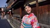 gueixa : beautiful lady with flower pattern kimono standing in the old street in Kyoto. young Japanese woman near wooden house in traditional culture dress in Ishibe alley on sunny day smiling lovely. Vídeos