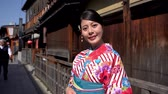 gueixa : japanese man people walking background on the old town path. young local lady with flower pattern kimono face camera smiling attractive. asian woman in traditional dress on ishibe alley kyoto japan.