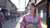gueixa : Urban city lifestyle asian woman in kimono costume walking on downtown street in kyoto japan. Happy young adult wearing japanese traditional dress kiyomizu zaka. teeming area many tourists visit.