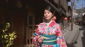 geisha : fast motion of vintage style local japanese woman wearing colorful traditional costume walking in kiyomizu zaka street. elegant lady in floral kimono clothing visit old town road in kyoto japan.