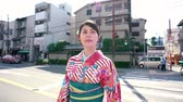 geisha : young elegant tourist woman wearing flower pattern kimono walking on urban road zebra crossing. girl traveler experience japanese culture in traditional dress in busy city street on sunny day. Stock Footage