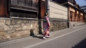 gueixa : fast motion of young japanese local girl in floral traditional costume walking on road in kyoto city japan. woman wearing flower pattern kimono walking through wooden house on urban road sunshine. Vídeos