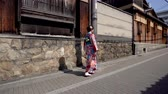 quimono : female tourist wearing kimono clothing visiting the old city in kyoto Japan. young girl traveler in floral japanese traditional costume walking on the road next wooden house in kiyomizu zaka street