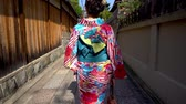 gueixa : back view of young local woman walking in old town path wearing floral kimono costume going home. japanese lady in traditional costume lifestyle join festival passing through wooden wall in street.